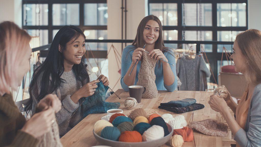 Vier junge Frauen stricken zusammen