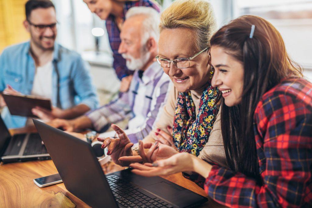 Junge Frau erklärt älterer dame den Computer