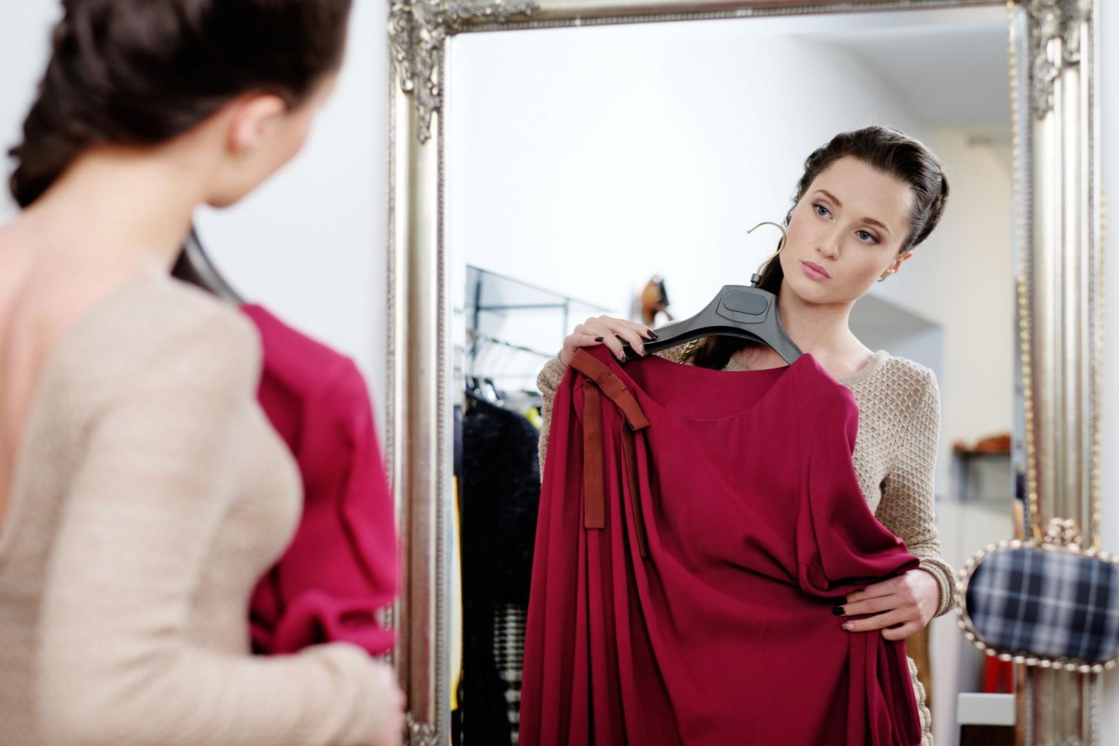 Junge Frau steht mit vorgehaltenem roten Kleid vor dem Spiegel