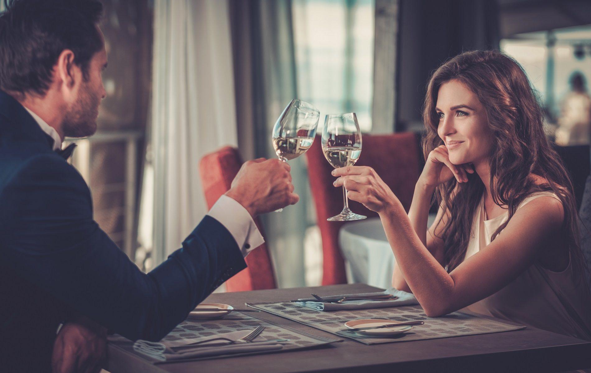 Schönes Paar sitzt im Restaurant und prostet sich zu
