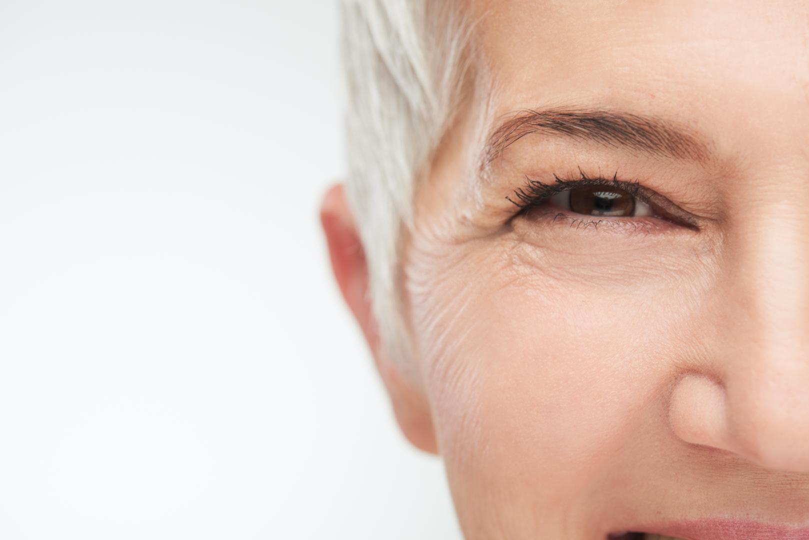 Das Bild zeigt die linke Gesichtshälfte einer Frau mittleren Alters mit kurzen grauen Haaren