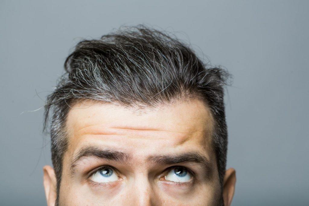 Obere Gesichtshälfte eines Mannes mittleren Alters mit leicht grauen Haaren.