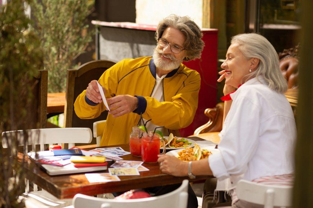 Paar mittleren Alters sitzt im Cafe und schaut Fotos an