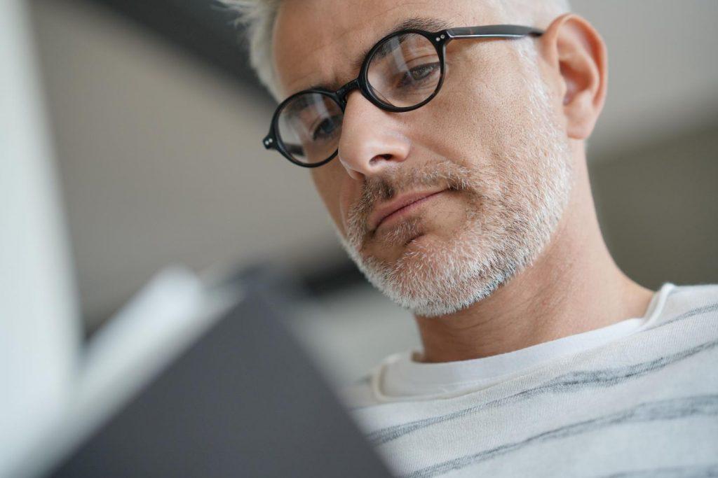 Grauhaariger Mann mit schwarzer Brille liest