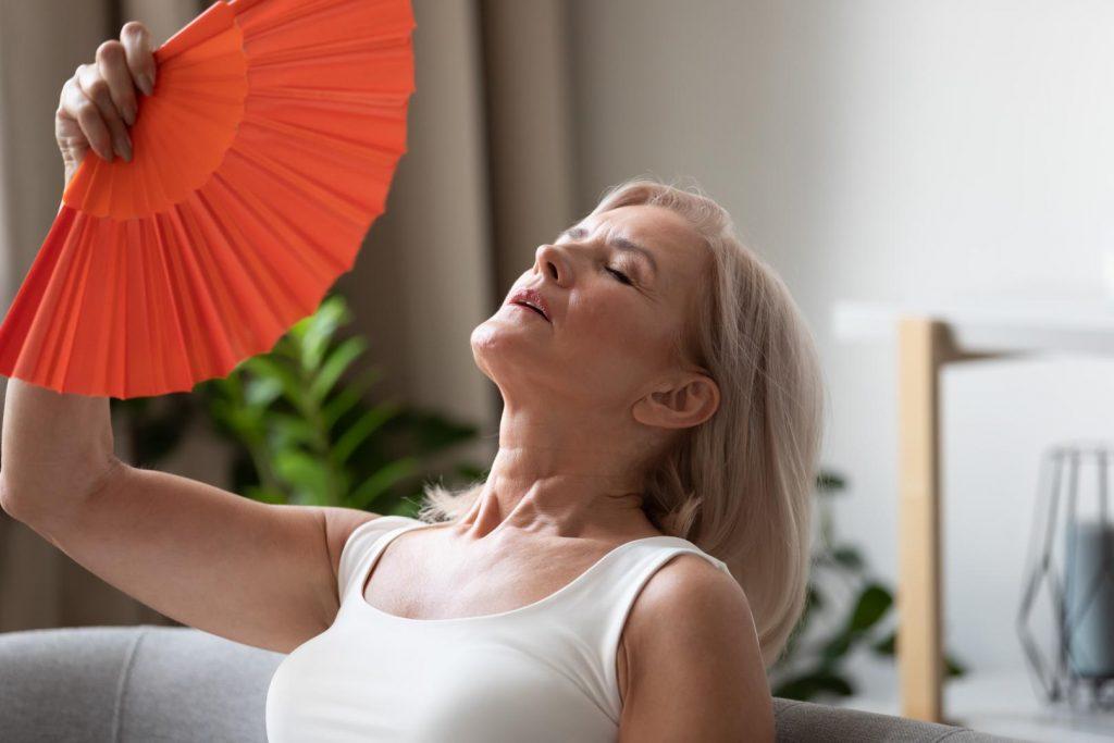 Frau mittleren Alters fächerst sich mit orangen Fächer Luft zu