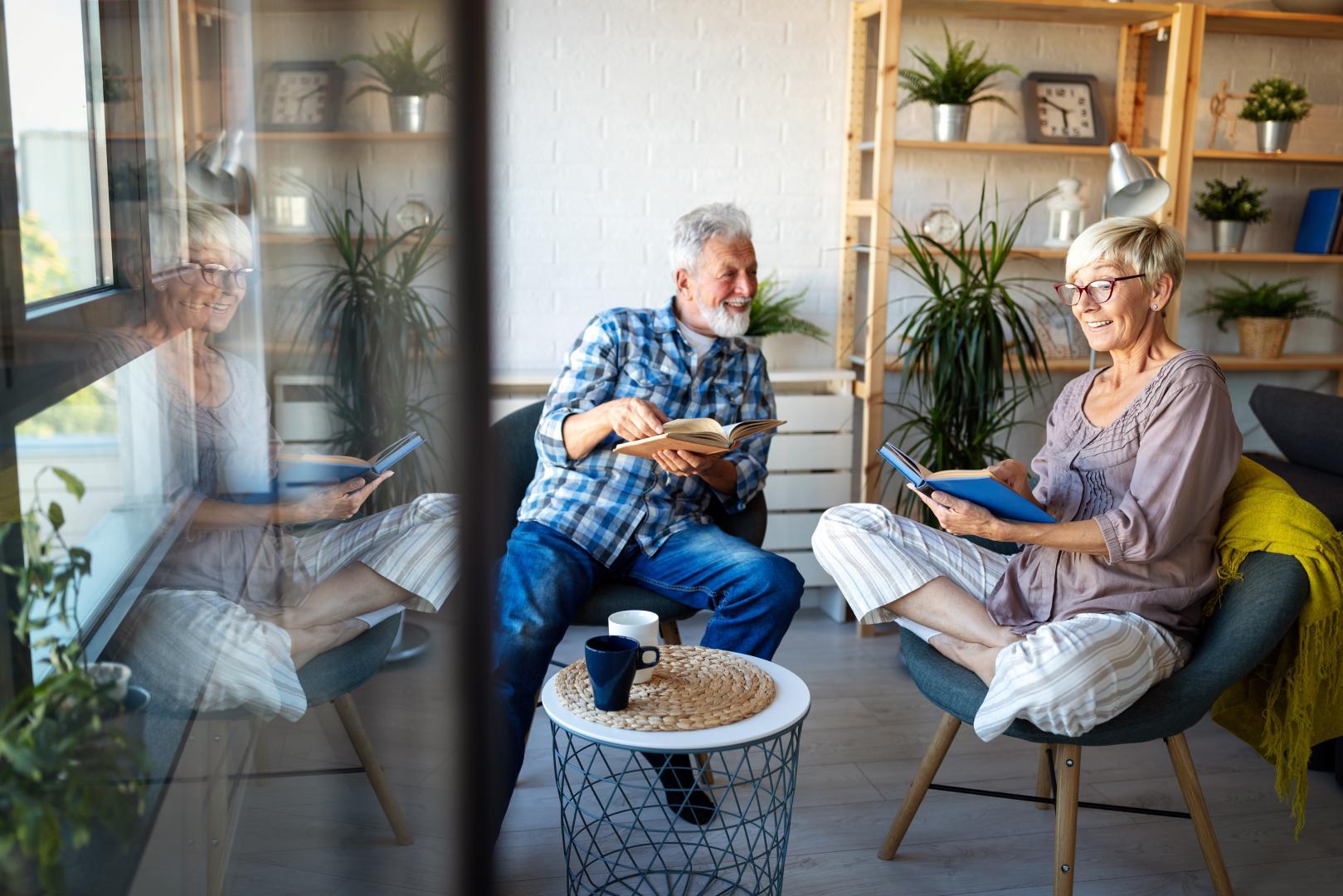 Reifes Paar sitzt gemütlich plaudernt im Wohnzimmer