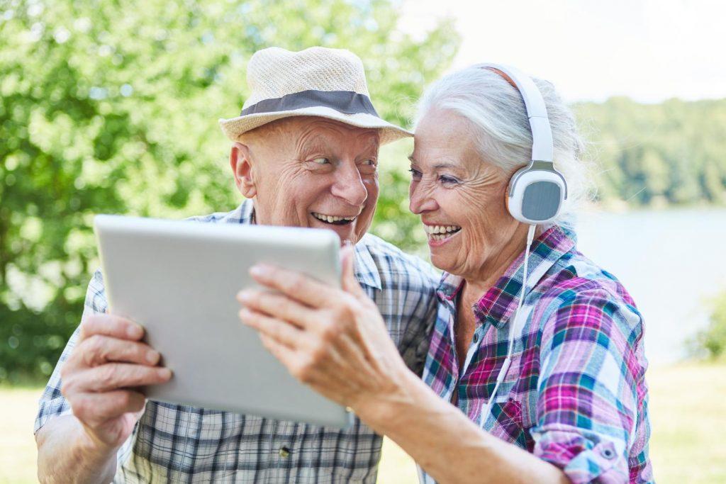 Älteres fröhliches Paar mit IPad in der Hand und Kopfhörer auf