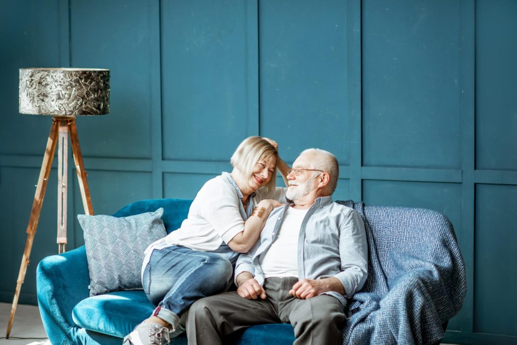 Reifes Paar sitzt gemütlich auf der Couch und lacht sich an