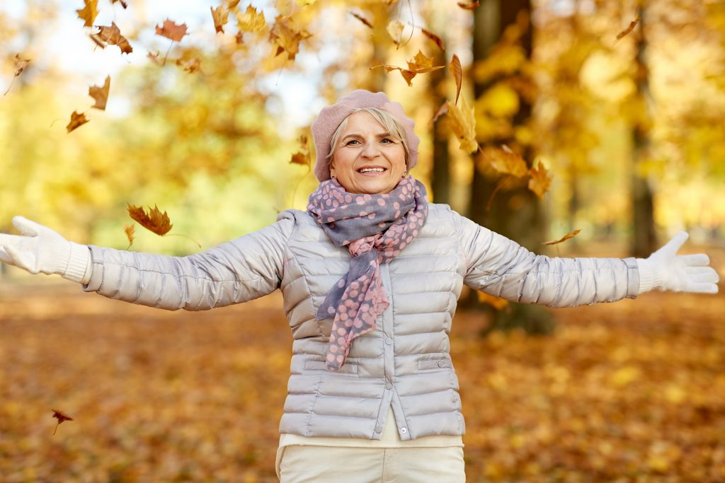 Fröhliche ältere Damen genießt den sonnigen Herbst