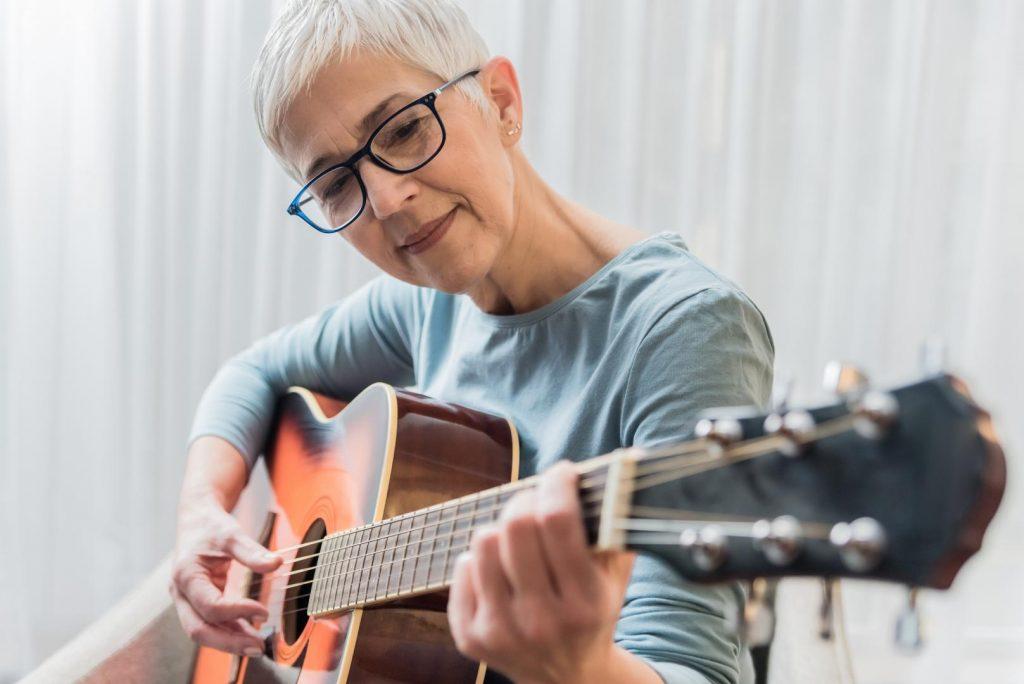 Reife Frau spielt Gitarre