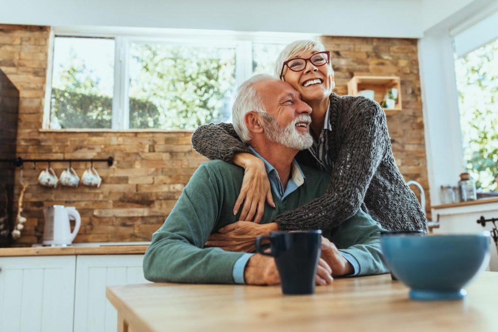 Älteres Paar umarmt sich glücklich am Küchentisch