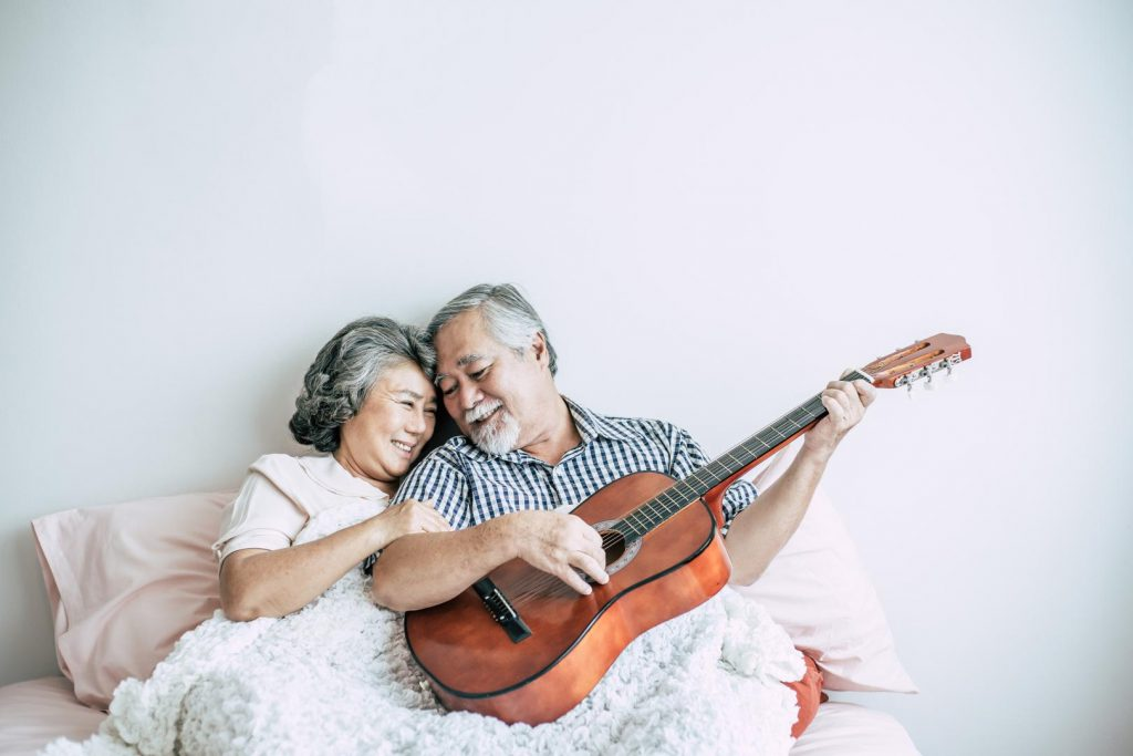 Älteres Paar liegt im Bett und der Mann spielt Gitarre
