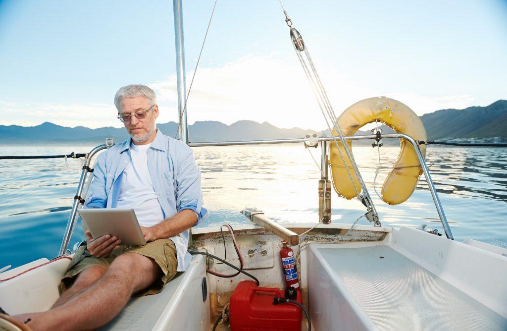 Älterer Herr sitzt entspannt mir seinem Tablett auf dem Segelschiff