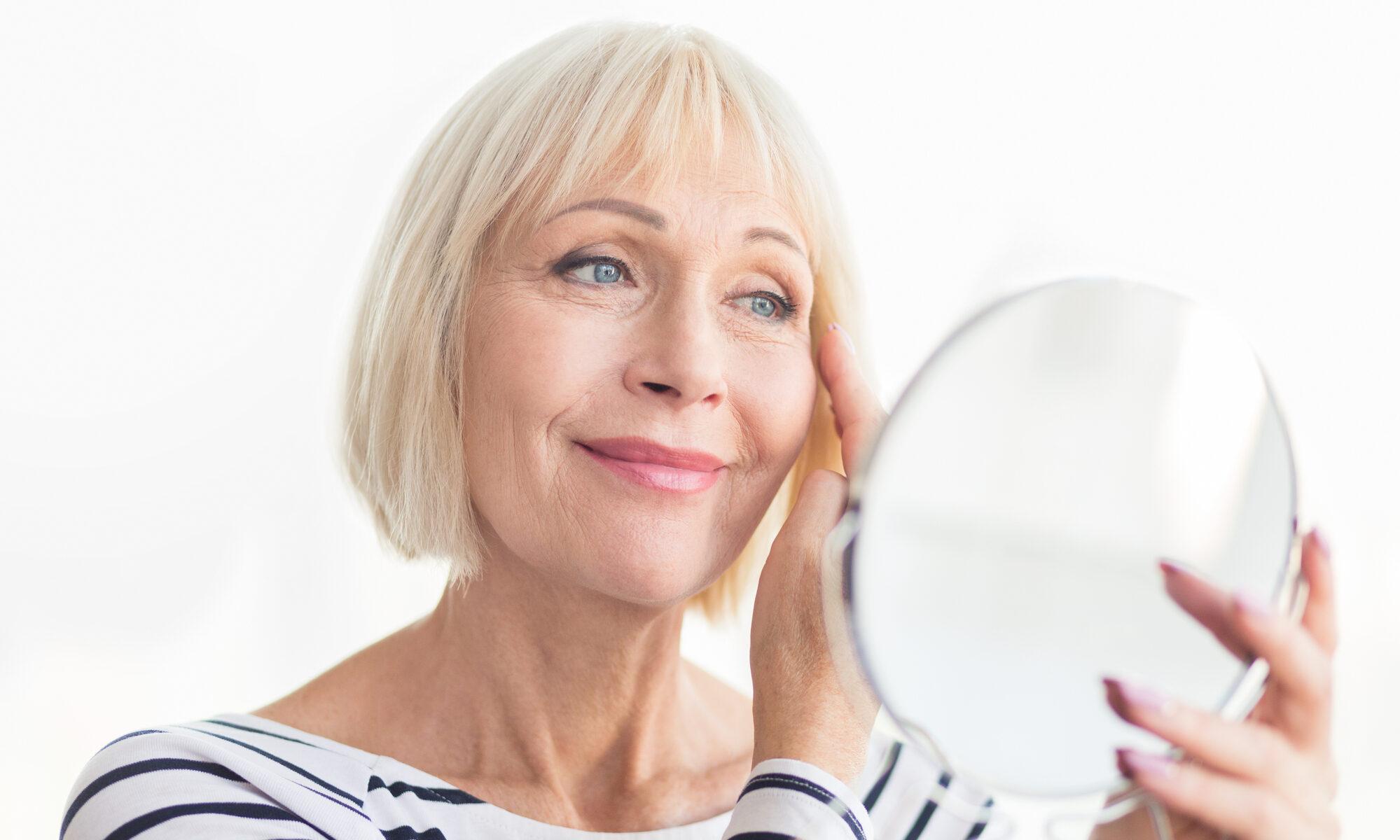 Ältere attraktive Frau schaut in den Handspiegel