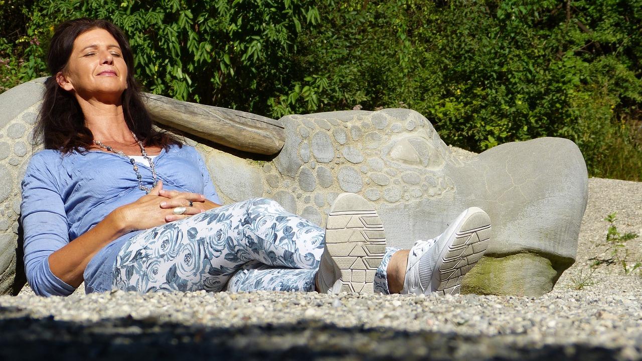 Frau mittleren Alters liegt entspannt in der Sonne